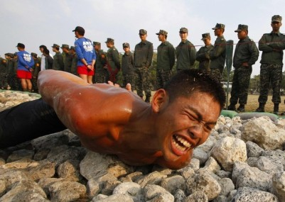"A trainee crawls through the Taiwan Marines frogmen ""Road to Heaven"" test in Zuoying, Kaohsiung, southern Taiwan, February 6, 2010. The ""Road to Heaven"" test, which is the final stage of a nine week intensive Amphibious Training Program, requires trainees to execute various exercises and leopard crawl along a 50 metre long path that is littered with jagged corals and rocks. REUTERS/Nicky Loh (TAIWAN - Tags: SOCIETY MILITARY)"